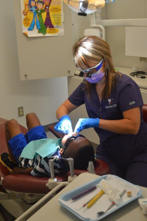 Dental hygienist cleaning a child's teeth at Healthy Smiles clinic.